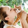 Asian woman kissing cat — Stock Photo