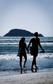 Silhouette of couple walking on beach at sunset holding hands — Stock Photo