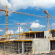 Building and cranes under construction against blue sky — Stock Photo #28395703