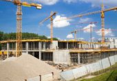 Building and cranes under construction against blue sky — Stock Photo