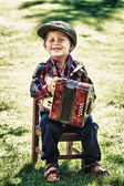 Happy young boy playing accordion in summer — Stock fotografie