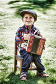 Happy young boy playing accordion in summer — Стоковое фото