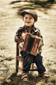 Happy young boy playing accordion in summer — Stockfoto