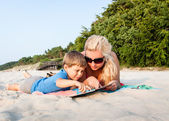 Mother and son sitting on sandy beach reading a book together — Stock Photo