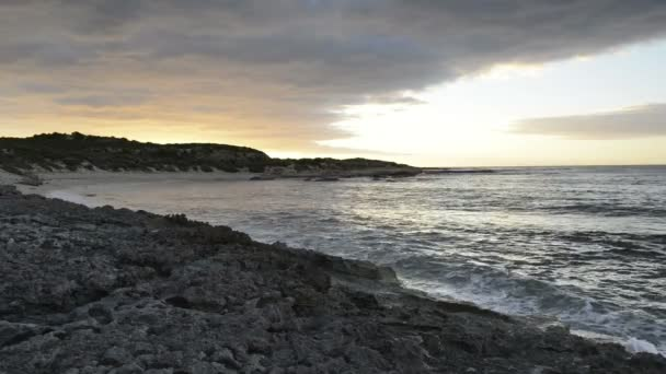 Olas del océano que traslapa la playa al atardecer — Vídeo de stock