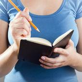 Kobieta pisze w notesie — Zdjęcie stockowe