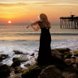 Fantasy scene with woman holding a violin at the ocean. — Stock Photo