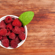 Stock Photo: Bowl of raspberries on old wooden table