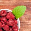 Stock Photo: Bowl of raspberries on an old wooden table