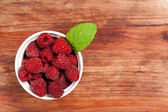 Bowl of raspberries on an old wooden table — Stock Photo