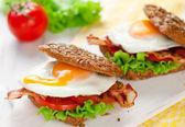 Sahanda yumurta ve domuz pastırması ile kepekli sandviç — Stok fotoğraf