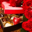 Box of chocolate truffles with red roses — Photo