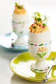 Stuffed eggs in egg cups — Stock Photo