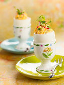 Stuffed eggs in egg cups — Stock Photo