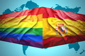 Waving Spanish and Gay flags — Stock Photo