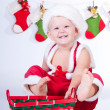 Cute baby Santa Claus with garlands and Christmas basket — Stock Photo