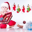 Cute baby Santa Claus with garlands and basket of Christmas toys — Stock Photo #13373864