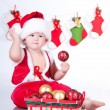 Stock Photo: Cute baby Santa Claus with garlands and basket of Christmas toys