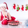 Cute baby Santa Claus with garlands and Christmas basket — Stock Photo #13499932