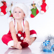 Cute baby Santa Claus with garlands of Christmas bootee — Stock Photo #13499933