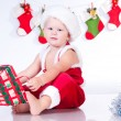 Cute baby Santa Claus with garlands and Christmas basket — Stock Photo #13499943