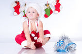 Cute baby Santa Claus with garlands of Christmas bootee — Stock Photo