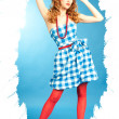 Pretty sexy redhead Pin Up girl in a checkered dress and red stockings adjusts the bow on her head — Stock Photo