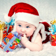 Cute little santa baby with New years gifts — Stockfoto