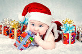 Cute little santa baby with New years gifts — Stock Photo