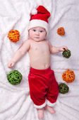 Little Santa Claus with toys lying on a white background. — Stock Photo