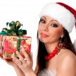 Beautiful brunette Santa Girl holding a gift box — Stock Photo