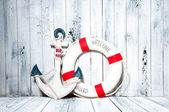 Anchor and life buoy on a background of white shabby wall boards. — Stockfoto