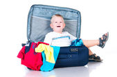 Small tourist collects things in a suitcase for travel — Stock Photo