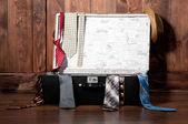 Valise vintage avec une cravate, contre un mur en bois. — Photo