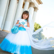 Little bride. A girl in a lush white and blue wedding dress and  — Stock Photo