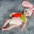 Small child with rabbit ears. Lying on your back with carrots. — Stock Photo