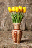 Yellow tulips in a wicker vase on background of hay. — Stock Photo