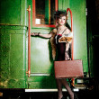 Retro girl with suitcase near the old train — Stock Photo