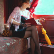 Retro girl reading book in  wagon train — Stock Photo