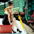 Retro girl sitting on suitcase at the train station — Stock Photo