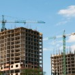 Construction of a high-rise building with a crane on the sky background. — Stock Photo