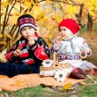Cute little girl and boy eating bagels in autumn park — Stock Photo
