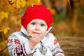 Cute little baby girl sitting in the forest and eating a bagel — Stock Photo