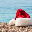 Stock Photo: Christmas hat lies on beach.