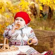Cute little baby girl sitting on rug in the woods and eating a b — Stock Photo
