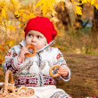 Cute little baby girl sitting in the forest and eating a bagel — Stock fotografie