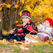 Cute little girl and boy eating bagels in autumn park — Стоковая фотография