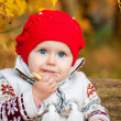 Cute little baby girl sitting in the forest and eating a bagel — Lizenzfreies Foto