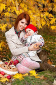 Happy family, mother and little daughter in autumn park — Stock Photo