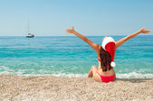 Girl on the beach in a Christmas hat. — Stock Photo